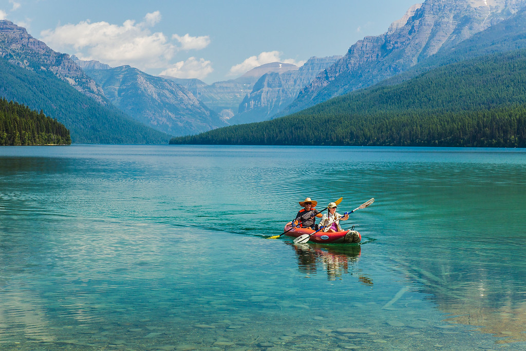 Photo of couple riding a kayak on bowman lake. Glacier National Park, Montana