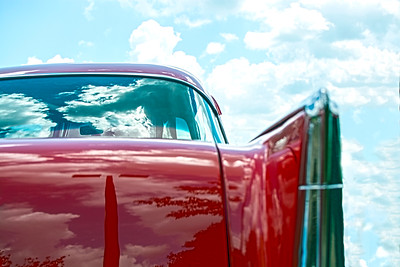 Red classic car with sky background