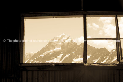 Old image effect. View Mount Cook through Hookers Track  trampers hut window