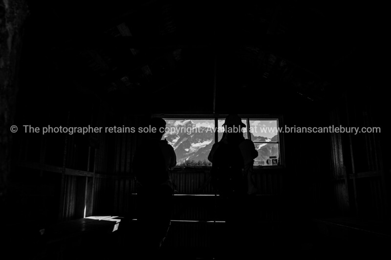 Trampers silhouetted as they look at mountain view through window of rustic mountain hut.