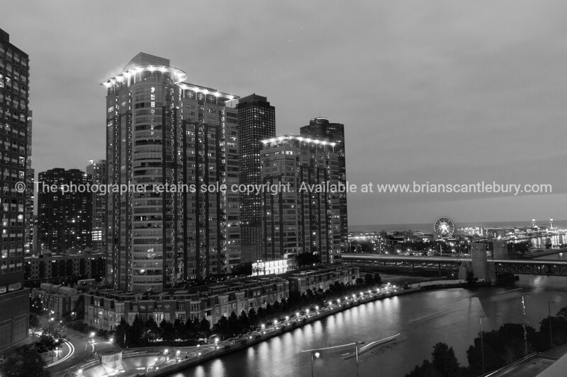 Chicago buildings, towering overhead, overground railway, urban road and lights streams with light flares from street lights, Illinois, USA. Looking from th east side to North and the highrise apartments, hotels and commercial buildings.