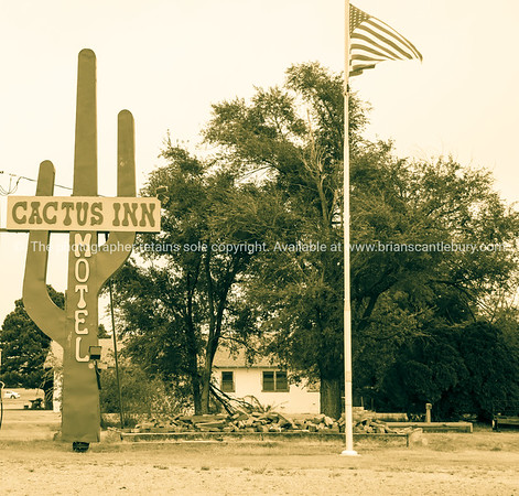Cactus Inn Motel sign and flagpole by pile of rubble