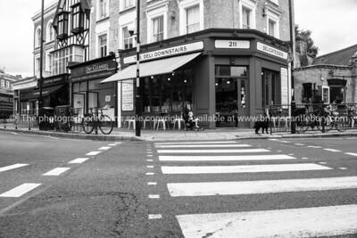 London, street scenes Bow, pedestrian crossing to deli across intersection.