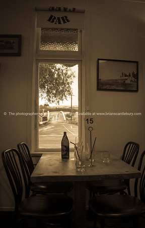 Old pub table with empty beer bottle.