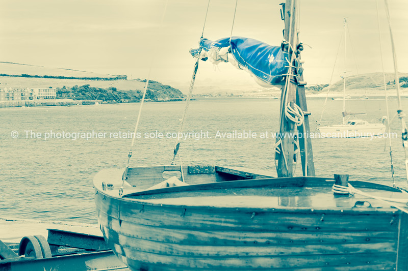 Clinker built sailing dinghy rigged and standing on lauch ramp at Padstow desaturated blue sail cover.