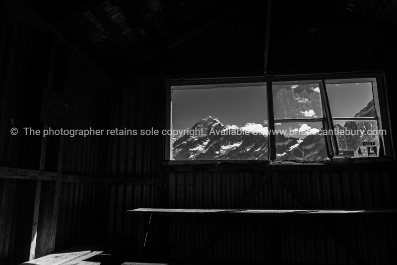 Sunrise sunshine strikes snow-capped Mount Cook appears through window like a picture from inside old trampers hut.