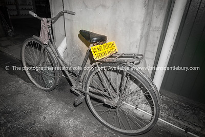 Dirty old pushbike leaning against wall in back street with bright yellow sign