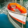 Bright orange and white painted wooden dinghy tied to pier at Boothbay