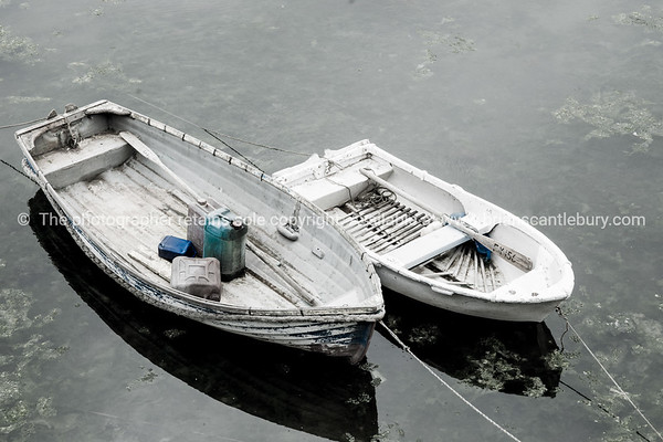 Two dinghies tied off to pier Mevigissey Cornwall.