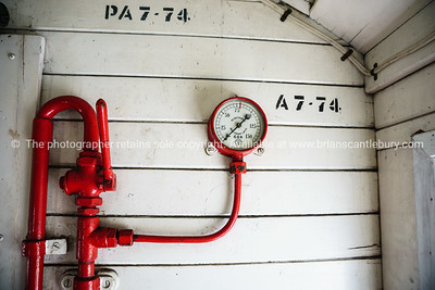 Old gauges. Red pipe spiders across the old timber wall lining.