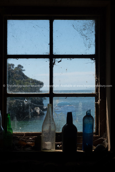 Old bottles standing on window sill of multi-paned window with view through to coastal scene