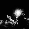Monochrome image of sun bursts and lens flare above cloud against blue sky