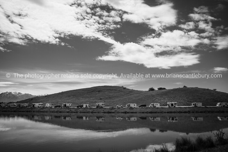 Twizel New Zealand - November 12 2020; Famous turquoise trout and salmon fishing destination Ohau Canal with trailer and mobile homes parked along siide and reflected in water at Twizel
