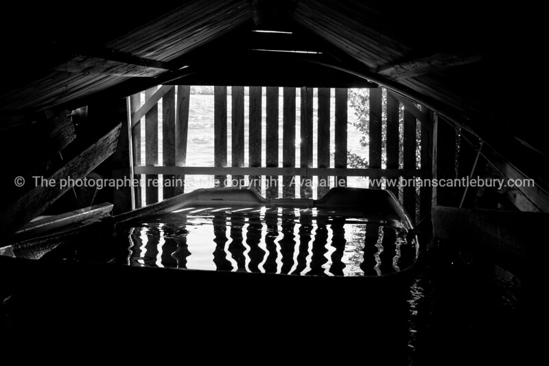 Interior of old wooden boatshed on side of lake with dinghy full of water.