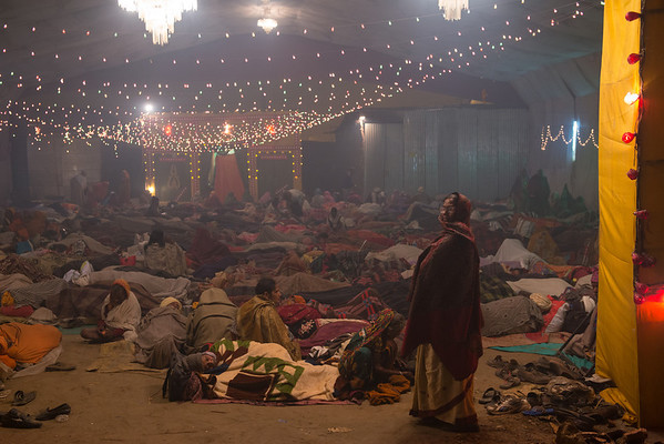Lone woman standing in the doorway to an Ashram, while people sleep behind her