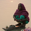 On the bank of the Ganga river an old Indian lady making her daily ritual blessing