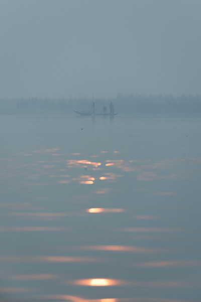 Reflection of the sunrise creating a silhouette of an early morning fishing boat, Varanasi, India