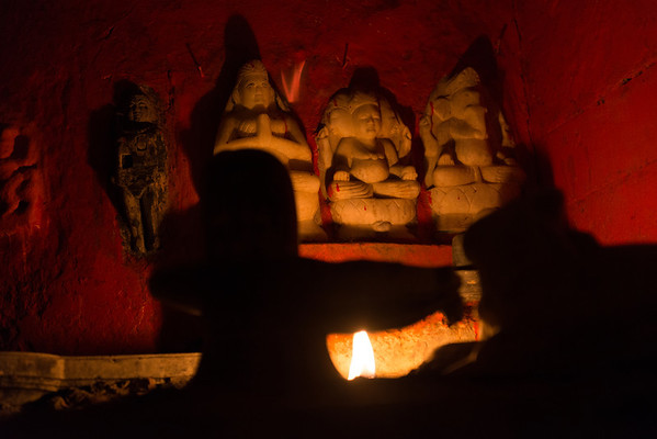 Miniature statues of deities lit by candle light, Varanasi, India