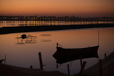 Sunset  over fishing boats and traps on the Ganga river with the lights of Maha Kumbh Mela in the background