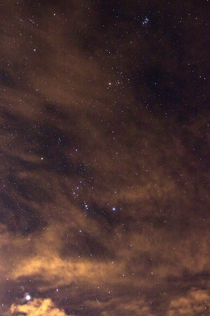 Stars partially obscured by high-level clouds at Gates Pass outside of Tucson, AZ. From bottom left to top right: Sirius (part of Canis Major), Orion, Taurus, and the Pleiades cluster