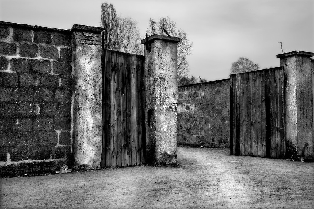 Entrance to Prison Cell Block, Sachsenhausen Concentration Camp<br /> <br /> On November 10, 1936, just months after Sachsenhausen was established as a concentration camp, the first of thousands of prisoners was murdered.  A communist and member of the Reichtag, he was shot as he attempted to escape.  The SS also targeted Jewish prisoners for persecution between December 1936 and February, 1937.<br /> <br /> Early in 1937, to deal with prisoners who violated camp discipline, a cell block was set up on the south-east perimeter of the camp next to the Jewish barracks.  Enclosed behind a high brick wall with a heavy wooden gate, this entrance was closely monitored at all times by the SS from watchtowers.<br /> <br /> The cell block was made of brick and had 3 wings.  It consisted of 80 cells in long rows and interrogation rooms.  Using this cell block as a special prison for official punishments, here the Gestapo carried out the most brutal punishments of all, mainly by prisoner beatings, both inside the cell block and outside.  <br /> <br /> Inside, prisoners were confined to darkness in locked, small single cells with no view to the outside.  Regular beatings on their lower backs as they bent over trestles were so severe that victims were unable to walk or sit down afterwards and some prisoners died. <br /> <br /> Outside the cell block was a series of tall wooden poles where prisoners were suspended by their wrists tied behind their backs.  Few survived the beatings that followed.  <br /> <br /> A number of prominent individuals were detained here, including Georg Elser, who is known for his failed attempt to assassinate Hitler on November 8, 1939.