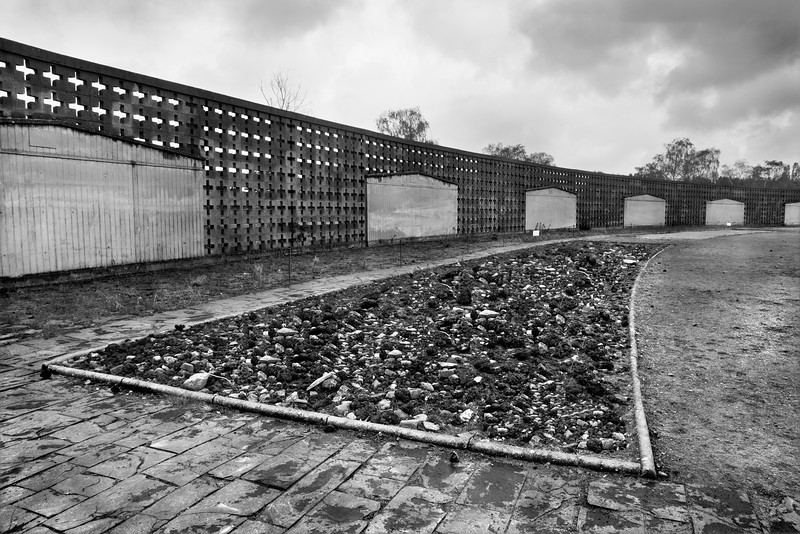 "Shoe-Testing track, Sachsenhausen Concentration Camp<br /> <br /> Sashsenhausen Concentration Camp was built in the form of a triangle.  The rows of barracks were grouped in a continuum around an axis in the roll-call area, all within view of the guards in Tower A, the pivotal point in the ""geometry of total terror."" <br /> <br /> The barracks, the façades of some of which are portrayed in the image, were simple constructions of wood.  Barracks contained 2 wings and each wing had a dayroom plus an extremely overcrowded dormitory with three-tiered bunks; each bunk sleeping 9 prisoners.  A shared open toilet area was located in the centre of the barrack between the 2 wings.<br /> <br /> A special ""shoe-testing"" track 700 metres long was laid out around the parade ground in front of the barracks.   This track, designed by a research institute, had 9 different types of surfaces, however, a combination of cement, cinders, broken stones, gravel and sand seemed to be predominant.   <br /> <br /> From 1940 on, the prisoners were part of a penal work detail to test shoes for local shoe manufacturers.  Regardless of the weather, prisoners were forced by the SS guards to wear new shoes and march at a brisk pace up to 40 kilometres a day around the track.  <br /> <br /> Should a prisoner not be able to keep up the pace, he was hit by the guards.  In 1944, the SS guards devised a special torture which was to make prisoners walk in shoes 1 or 2 sizes too small, while carrying sacks filled with 20 kilograms of sand.<br /> <br /> Most prisoners did not survive this brutal torture for more than a week or so."