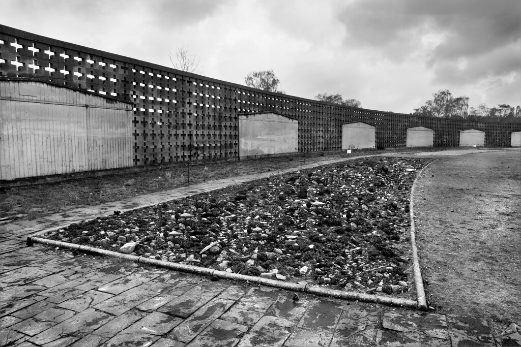 """Shoe-Testing track, Sachsenhausen Concentration Camp<br /> <br /> Sashsenhausen Concentration Camp was built in the form of a triangle.  The rows of barracks were grouped in a continuum around an axis in the roll-call area, all within view of the guards in Tower A, the pivotal point in the """"geometry of total terror."""" <br /> <br /> The barracks, the façades of some of which are portrayed in the image, were simple constructions of wood.  Barracks contained 2 wings and each wing had a dayroom plus an extremely overcrowded dormitory with three-tiered bunks; each bunk sleeping 9 prisoners.  A shared open toilet area was located in the centre of the barrack between the 2 wings.<br /> <br /> A special """"shoe-testing"""" track 700 metres long was laid out around the parade ground in front of the barracks.   This track, designed by a research institute, had 9 different types of surfaces, however, a combination of cement, cinders, broken stones, gravel and sand seemed to be predominant.   <br /> <br /> From 1940 on, the prisoners were part of a penal work detail to test shoes for local shoe manufacturers.  Regardless of the weather, prisoners were forced by the SS guards to wear new shoes and march at a brisk pace up to 40 kilometres a day around the track.  <br /> <br /> Should a prisoner not be able to keep up the pace, he was hit by the guards.  In 1944, the SS guards devised a special torture which was to make prisoners walk in shoes 1 or 2 sizes too small, while carrying sacks filled with 20 kilograms of sand.<br /> <br /> Most prisoners did not survive this brutal torture for more than a week or so."""