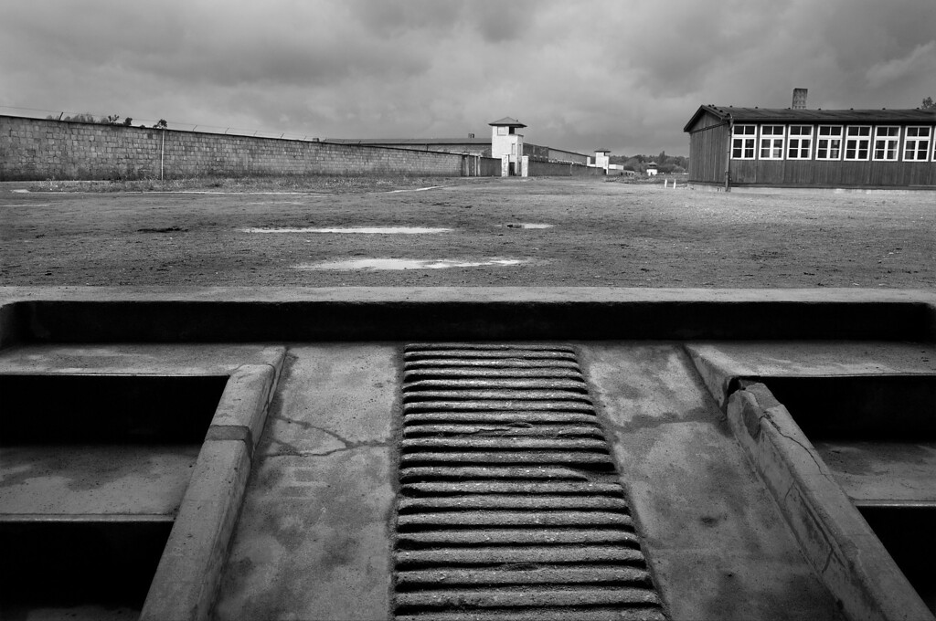 """View From Pathology Building, Sachsenhausen Concentration Camp<br /> <br /> From the beginning of Sachsenhausen in 1936, on the south-western edge of the prisoners' camp, stood the infirmary, an integral part of the complex to """"look after"""" ill prisoners.  In 1941, the SS had a pathology building constructed, which consisted of an autopsy room and a large mortuary in the cellar.  This building exists today in its original form.<br /> <br /> The view from the front of the pathology building, taken from the """"corpse slide"""" which leads to the cellar below, is commanding.  Looking to the far northern end of the western wall, in a strategic position at the apex of the triangular prisoners' camp, is Tower E, with its circular viewing deck.  This key watchtower is one of 9 in total, all of which were manned by SS guards at all times.  Southward along the perimeter from Tower E can be seen two more watchtowers.<br />  <br /> Also in view is an end section of Barrack R I, one of the two remaining 1936 infirmary barracks.  By the end of the war, there was a total of 6 barracks with fewer than 800 beds, but holding in excess of 2,000 patients.  Only Jewish prisoners were denied any treatment in the infirmary. <br />  <br /> Under the supervision of the camp doctors, the sick were primarily tended by other prisoners called """"inmate medical assistants."""" Generally known amongst the prisoners as """"medics,"""" most had no idea of medicine at all.  <br /> <br /> From 1936 to 1945, the role of the infirmary changed a number of times from providing minimal treatment to inmates, to a place of medical experiments, medical crimes and deliberate extermination of thousands by SS doctors, while at the same time, a huge propaganda showcase."""