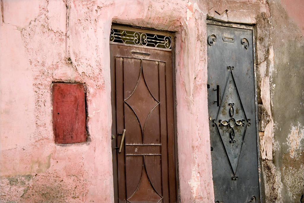 "Doors to private quarters, Marrakech<br /> <br /> In the medina, Marrakech, the famous ""red city"" doors are recessed into the pink plaster walls.  The decorative triangles on the doors are a symbol of the Berbers, an ethnic group indigenous to Northern Africa."
