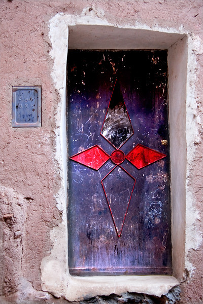 Ornate door in Tinerhir<br /> <br /> In the lively town of Tinerhir, situatd in the southern oases on the southern edge of the High Atlas, the light is intensely bright.  Natural colours are rich and inhabitants extend the magic of hues to their dwellings.