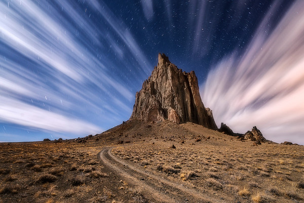The Shiprock volcanic rock formation under the moonlight and clouds during a long exposure.