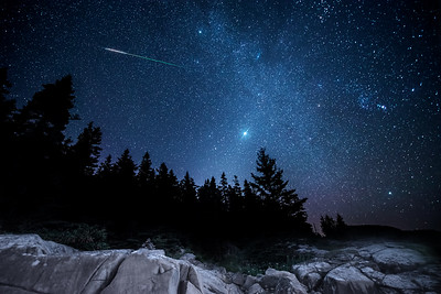 A bright meteor shoots through the night sky in one frame of an hour long time lapse I set up on some rocks on the Bold Coast of Maine. Photographed September 7, 2013.