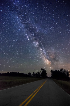 """""""Road To The Milky Way II"""" - a meteor shoots through the sky next to the Milky Way as it rises above Parmenter Rd in Palermo, Maine. This area is also known as Mo's Mountain. Photographed June 10, 2013."""