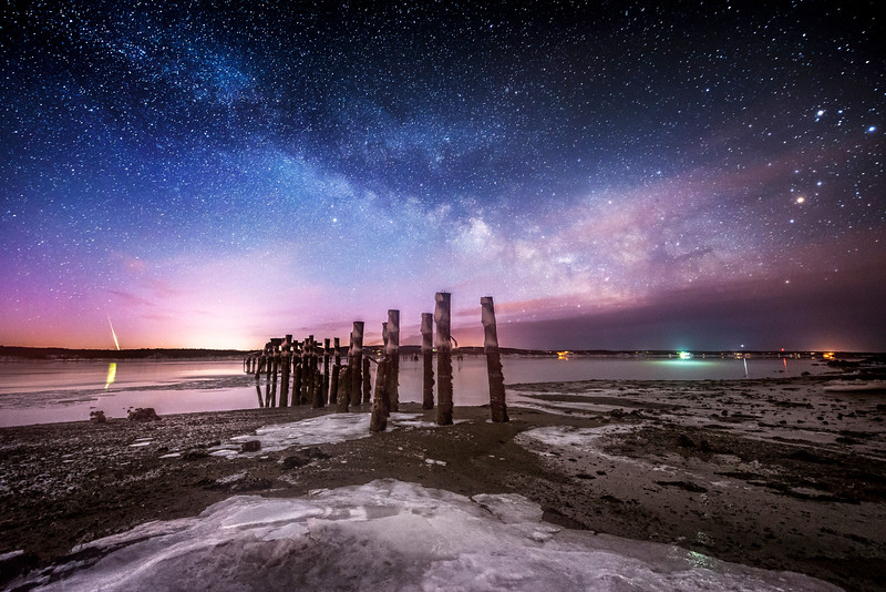 After a few months of planning our second astrophotography shoot of 2015, the frigid temperatures here in Maine didn't stop us from going out to time lapse the rise of the Milky Way over the Penobscot River next to the old pilings at Sandy Point Beach. On the left side of this image a brilliant green fireball streaks down towards the horizon and leaves a bright reflection on the water.