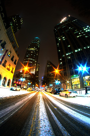 snow covered road in the city at night
