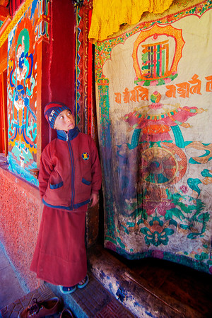Little Monk guards the monastery door while elders prepare for the mask dance routine.