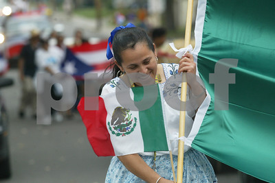 The month-long Hispanic Heritage celebration continued Saturday with a parade through the streets of Geneva, and food and music in the city's Seneca Street parking lot. Crescencia Aguilera, formerly of Mexico and now living in Geneva, helps carry the Mexican national flag through a strong wind. Following her is a contingent representing Puerto Rico. 9/28/03