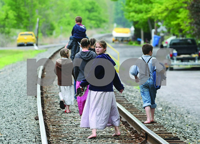 Spencer Tulis / Finger Lakes Times This group of young Mennonites take a country stroll along the railroad tracks in the town of Bentoon recently.