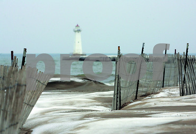 Spencer Tulis / Finger Lakes Times A small covering of snow mixes with the sand at a vacant Sodus Point beach Saturday.