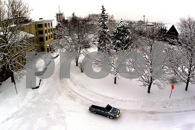 A car drives slowly around Park Place in Geneva after a big snow storm. 3/5/01