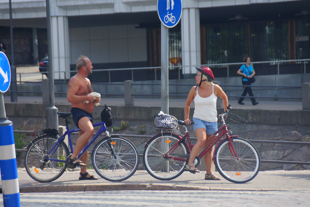 A Finnish man without a shirt and a lady stop on their bicycles to take a break and drink some water in Helsinki, Finland