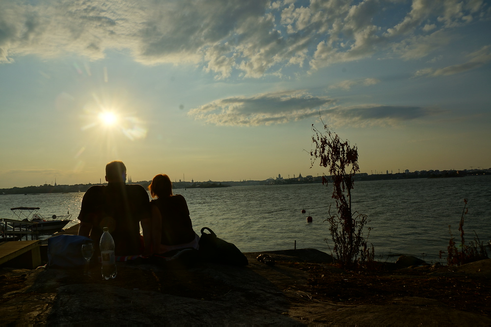 A couple enjoying a picnic and a bottle of wine while waiting for sunset on the recently opened Lonna Island in Helsinki, Finland