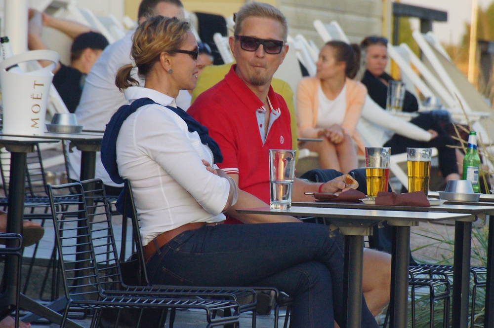 A couple enjoying a beer nearby the carpet washing docks in Helsinki, Finland