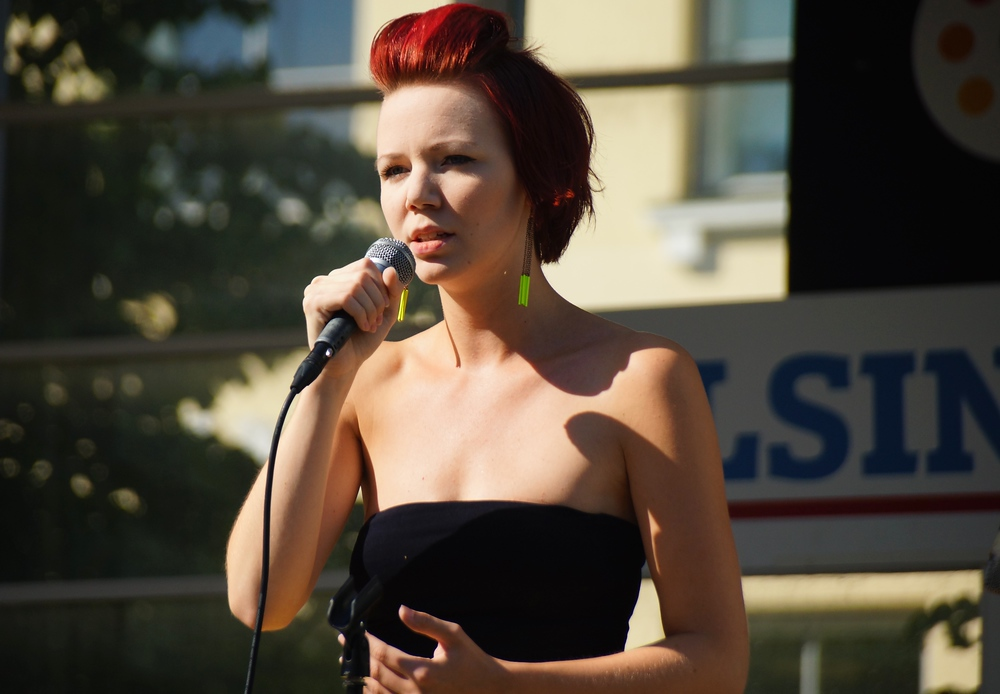 A talented Finnish female performer singing on stage in downtown Helsinki, Finland