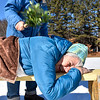 Jane Potsaid is hit with dried branches by her husband Mike Potsaid at the third stage of the wife carrying race held at the Saima Park Finnish Center in Fitchburg on Saturday Feb. 4, 2017. (Sentinel & Enterprise photo/Jeff Porter)