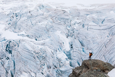 Climber contemplates the icecliff-threatened descent into the Donne Valley beneath Taoka Icefall, Darran Mountains, Fiordland.