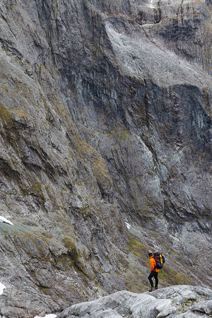Climber stands on rock ledge in Donne Valley beneath Karetai Peak