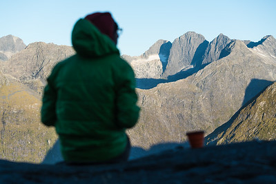 A climber takes in the view from Sheerdown Peak to Sabre Peak, Darran Mountains, Fiordland National Park