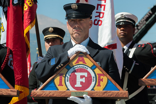 COLORADO SPRINGS - Fitchburg firefighter Patrick Haverty stands by to present a memorial flag to Debbie Jeffries, sister of Jack Mulchay, during the Fallen Firefighters Memorial Ceremony in Colorado Springs. Behind Haverty is Fitchburg Fire Lt Robert Dacosta carrying the flag of the department. Saturday September 15, 2018 [Photo/Jim Marabello]