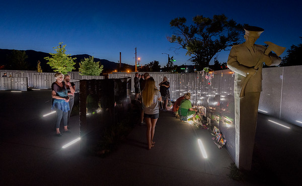COLORADO SPRINGS - A firefighter carved into the granite of the walls stands guard as families linger into the night after the IAFF Fallen Firefighter Memorial in Colorado Springs.  Saturday September 15, 2018 [Photo/Jim Marabello]